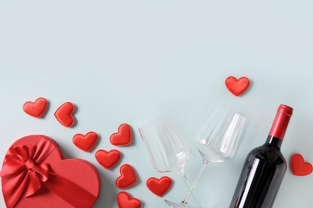 Valentijnsdag geschenk, harten en rode wijn op blauwe, romantische wenskaart.