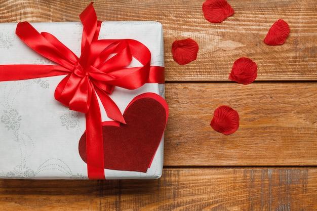 Valentijnsdag geschenk in witte doos en harten en bloemblaadjes op houten achtergrond