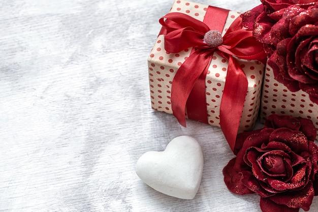Valentijnsdag geschenk met decoratieve rozen en wit hart op lichte achtergrond kopie ruimte.
