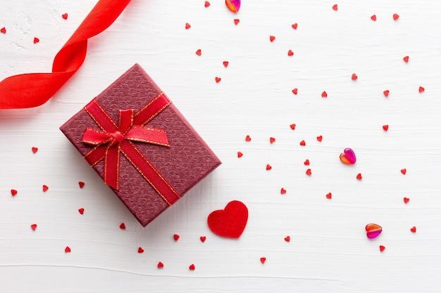 Valentijnsdag geschenk met lint op witte houten tafel bezaaid met rode harten