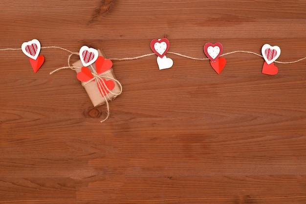 Valentijnsdag geschenk met rode harten op houten achtergrond.