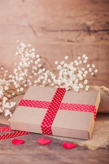 Valentijnsdag geschenk met rood lint op hout