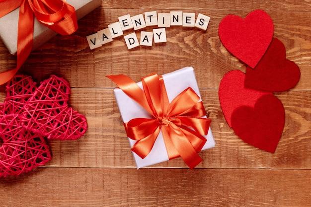 Valentijnsdag geschenk op houten achtergrond. harten en vakantiedecor op tafel.
