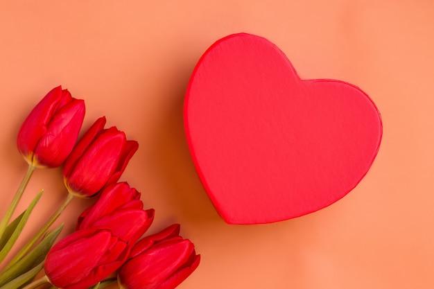 Valentijnsdag geschenk. rode tulpen met hartvormige doos op bruine achtergrond