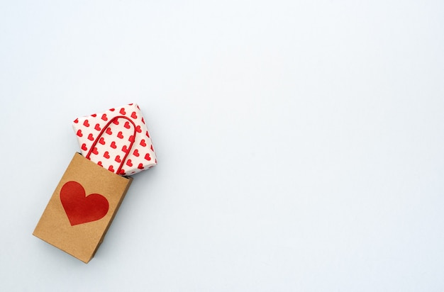 Valentijnsdag geschenkdoos met papieren mini tas op grijze achtergrond. kopieer ruimte