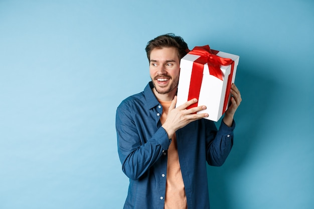 Valentijnsdag. glimlachende man die wat in geschenkdoos raadde, kreeg cadeau van minnaar vriendin, staande tegen een blauwe achtergrond. kopieer ruimte