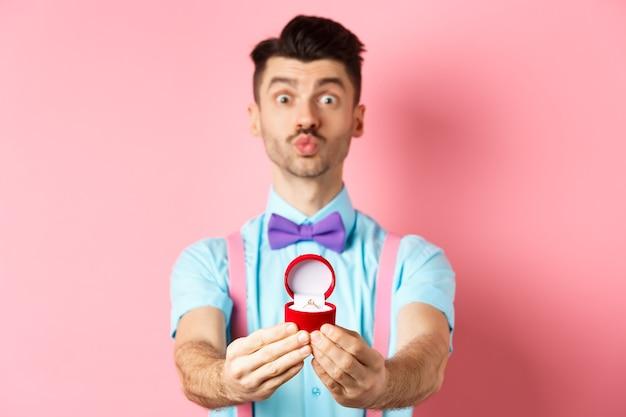 Valentijnsdag. grappige jonge man tuit lippen voor kus en verlovingsring tonen, voorstel doen, zeg met me trouwen met minnaar, staande over roze achtergrond.