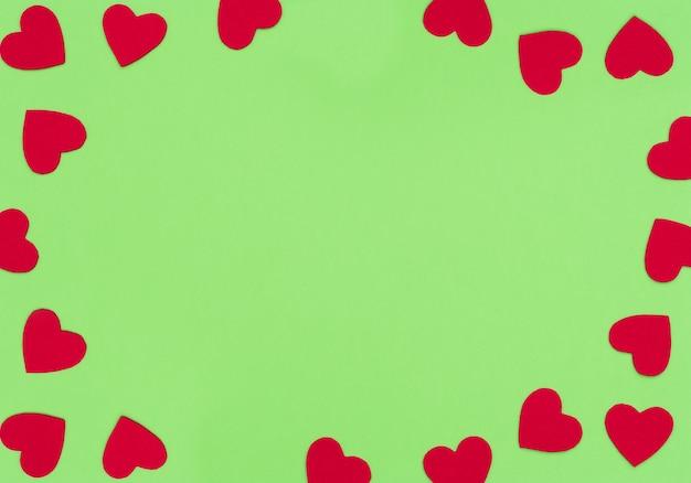 Valentijnsdag groene achtergrond met veel heldere vilt rode harten