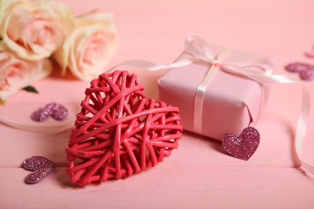 Valentijnsdag hart decoratie, boeket en geschenken op roze achtergrond