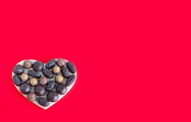 Valentijnsdag hartvormige doos met chocolade op een rood