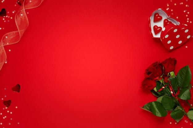 Valentijnsdag, hou van daten. boeket rozen met hartvormig chocoladesnoepjes en confetti eromheen op rood