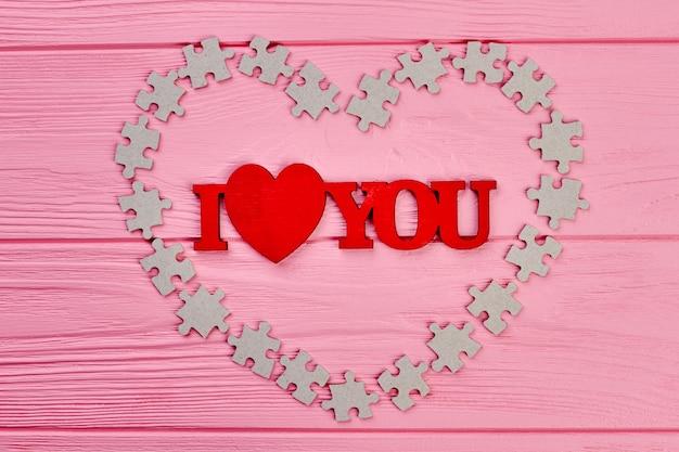 Valentijnsdag houten achtergrond. rode inscriptie ik hou van jou en hart gemaakt van kartonnen puzzels. fijne valentijnsdag.