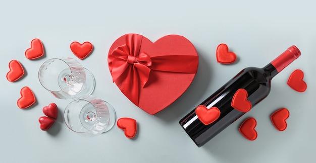Valentijnsdag ingesteld voor partij van rode wijn en wijnglazen en hart cadeau op blauwe achtergrond.
