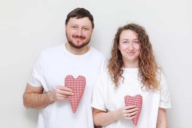 Valentijnsdag. jonge smily man en vrouw in witte t-shirts met rode harten in hun handen.
