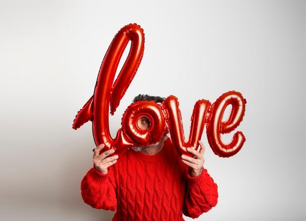Valentijnsdag. jongen die een ballon met het woordliefde op witte achtergrond met exemplaarruimte houdt.