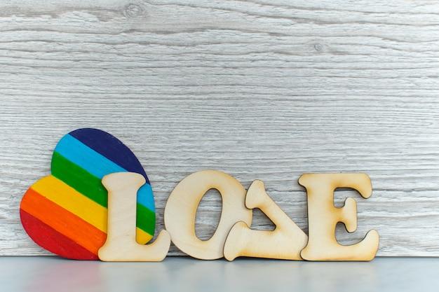 Valentijnsdag kaart achtergrond, regenboog schattig hart zoals een lgbt-trots regenboogvlag met hart in papier en decoratief houten woord. valentijnsdag romantisch. houd van mensenrechten en vrijheidconcept