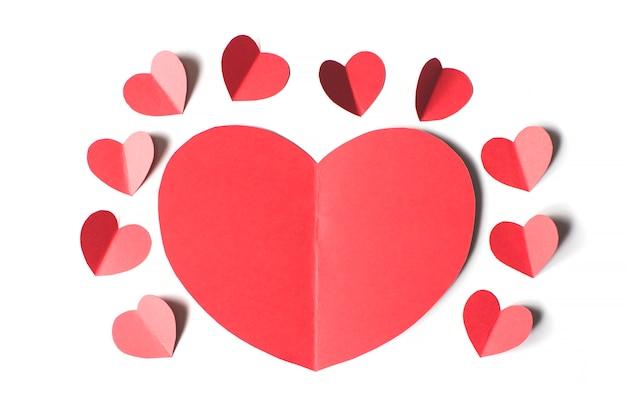 Valentijnsdag kaart concept, groot rood hart omringd door kleine rode harten op een witte achtergrond, papier knippen stijl.