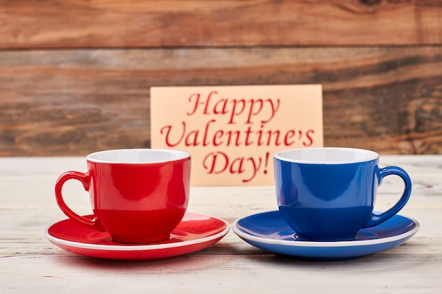 Valentijnsdag kaart en kopjes. lege rode en blauwe mokken. liefde geeft je energie.