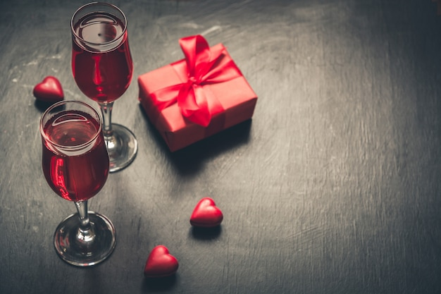 Valentijnsdag kaart met champagne en hart snoep op zwart.