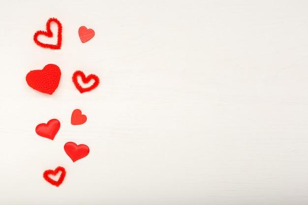 Valentijnsdag kaart met kopie ruimte, frame. witte houten achtergrond met rode harten. concept van valentijnsdag, liefde, romantiek, hart. valentijnsdag samenstelling, patroon. bovenaanzicht, plat gelegd.
