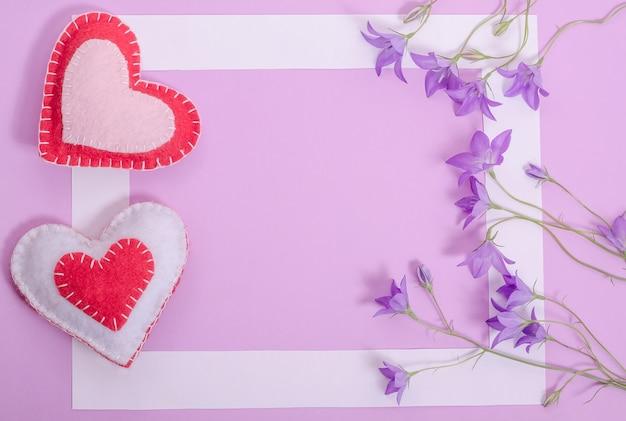 Valentijnsdag kaart met kopie ruimte, wit frame op lila achtergrond met hartjes en bloemen klokken