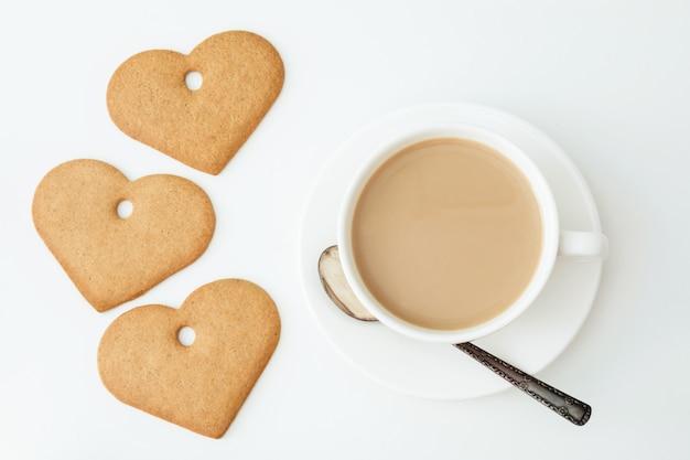 Valentijnsdag kaart. ontbijt. witte kop koffie met melk en koekjes op wit. bovenaanzicht