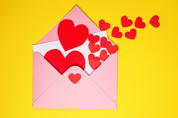 Valentijnsdag kaart. papieren rode harten vliegen uit roze papieren envelop op gele achtergrond. papierkunst op valentijnsdag. papier knippen en ambachtelijke stijl. ruimte voor tekst. concept van valentijnsdag