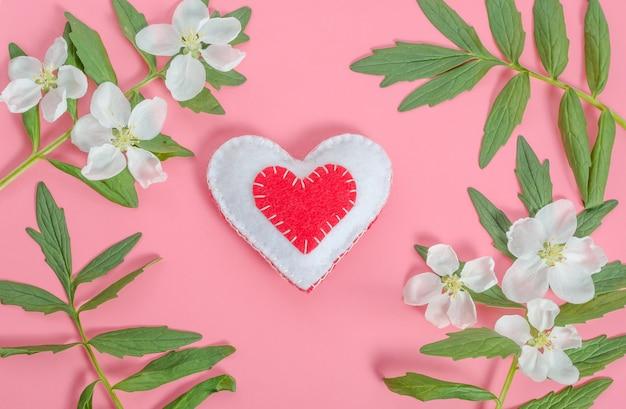 Valentijnsdag kaart, rood hart met een frame van bloemen en bladeren op een roze achtergrond