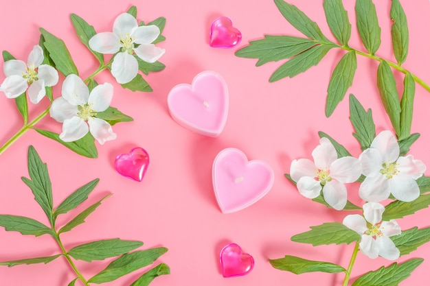 Valentijnsdag kaart, twee kaarsen in de vorm van roze harten met een frame van bloemen en bladeren op een roze achtergrond
