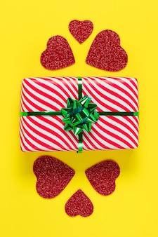 Valentijnsdag kaart. verpakt cadeau. minimalistisch ontwerp. feestelijk heden en rode harten op een geel papier achtergrond, romantische symbolische viering van liefde en genegenheid.