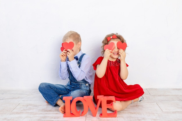 Valentijnsdag kinderen. een jongen en een meisje zitten met een grote inscriptie love en houden harten in hun handen
