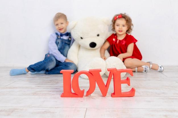 Valentijnsdag kinderen. jongen en meisje zitten met een grote teddybeer, de inscriptie liefde in focus