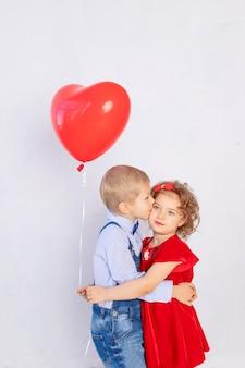 Valentijnsdag kinderen. jongen kust meisje vijf jaar oud met rood balhart