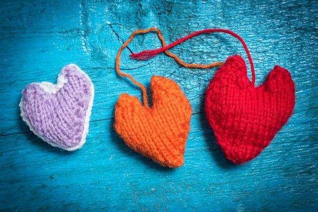Valentijnsdag. kleurrijke gebreide harten. rood hart op de blauwe planken. valentijnsdag. hart hanger. rood hart. valentijn kaarten.