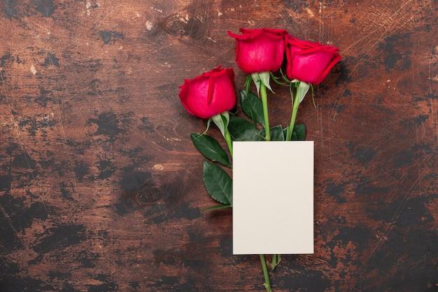 Valentijnsdag lege kaart met rood roze bloemen op vintage houten achtergrond