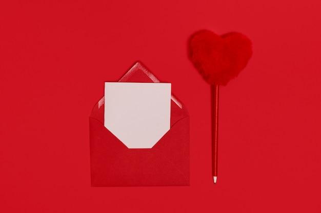 Valentijnsdag. lege sjabloon voor romantische letters in een envelop op een rode ruimte. pluizige rode hartvormige pen. flat lei. uitzicht van boven.