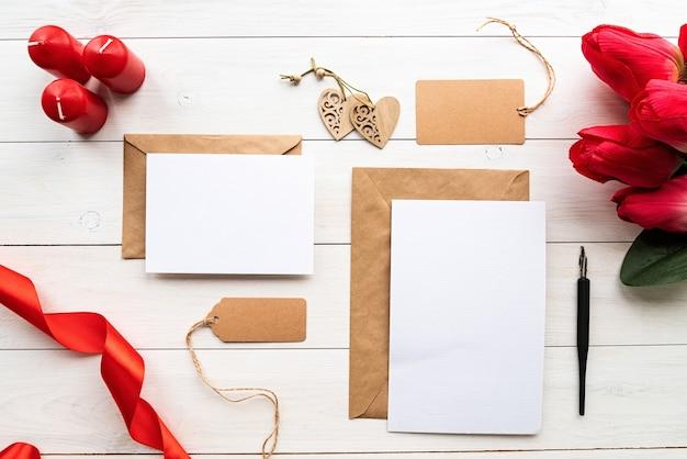 Valentijnsdag. lege wenskaarten met enveloppen en rode linten mock-up sjabloon voor valentijnsdag Premium Foto
