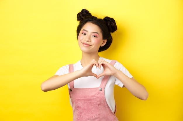 Valentijnsdag. leuk aziatisch meisje dat haar liefde verzendt, hartgebaar toont en bij romantische camera glimlacht, die zich op gele achtergrond bevindt