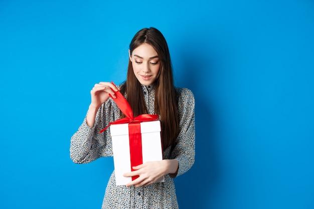 Valentijnsdag. leuke jonge vrouw open doos met cadeau, startlint van heden en glimlachend geïntrigeerd, staande op blauwe achtergrond.