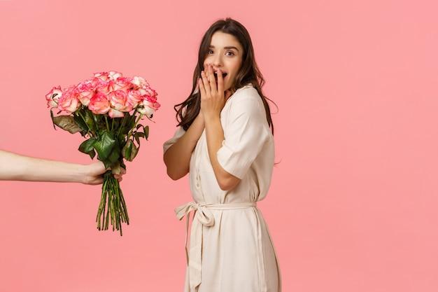 Valentijnsdag, levering en schoonheid concept. verbaasde vrouw hijgend en verrast als iemand haar prachtige boeket bloemen geeft, gefeliciteerd met jubileum, roze muur