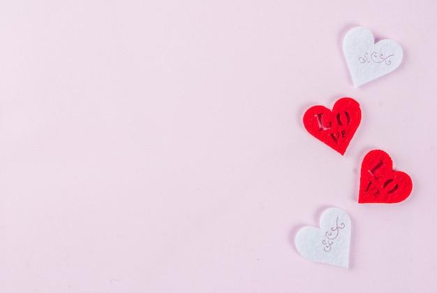Valentijnsdag licht roze achtergrond wenskaart concept twee rood hart en twee witte harten decoratie