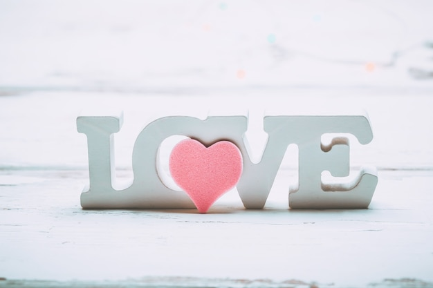 Valentijnsdag liefde concept. houten witte letters liefde met roze hart op witte houten achtergrond