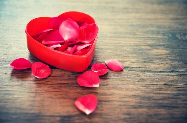 Valentijnsdag liefde hart concept open rood hart doos versierd met rode rozen bloemblaadjes op houten