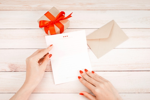 Valentijnsdag liefdesbrief op houten achtergrond. bruine envelop, roze notitie en geschenkdoos op tafel. vrouwelijke handen met rode nagellak