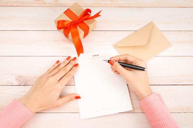 Valentijnsdag liefdesbrief op houten achtergrond. rode fluwelen hartvormige koekjes, snoep en koffie. vrouwelijke handen met rode nagellak