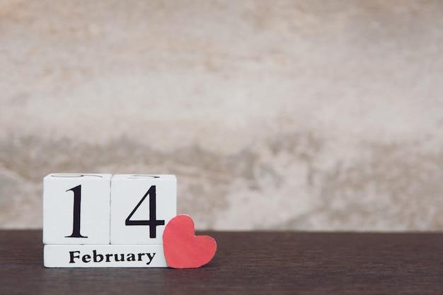 Valentijnsdag met 14 februari. houten witte blokkalender op houten lijstachtergrond met exemplaarruimte