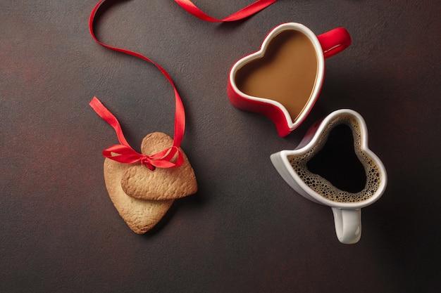 Valentijnsdag met geschenken, een hartvormige doos, kopjes koffie, hartvormige koekjes, bitterkoekjes en een schoolbord.