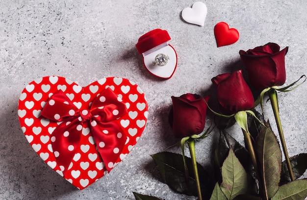 Valentijnsdag met me trouw verlovingsring in doos met rode rozen boeket en geschenk doos hart