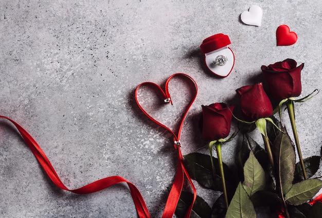 Valentijnsdag met me trouw verlovingsring in vak met rode rozen boeket en lint hart