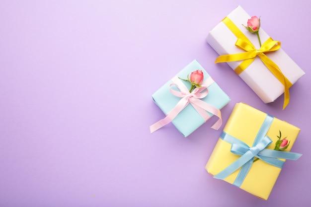 Valentijnsdag met roze rozen en geschenkdoos op violet
